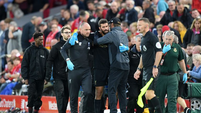 Alisson hobbles off during Liverpool v Norwich at Anfield