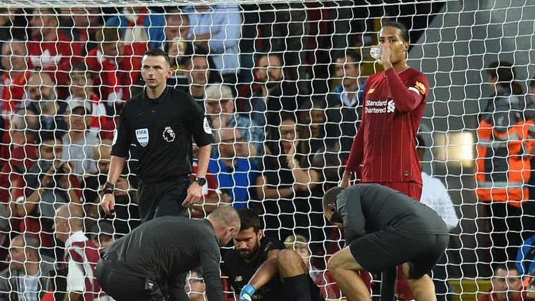 Alisson receives medical attention during Liverpool's match vs Norwich City