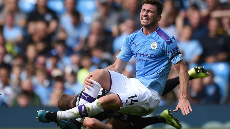 Laporte clutches his knee after a challenge with Brighton's Adam Webster