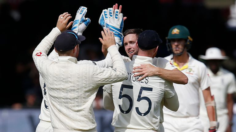 England's Chris Woakes (C) celebrates taking the wicket of Australia's Steve Smith for 92 runs during play on the fourth day of the second Ashes cricket Test match between England and Australia at Lord's Cricket Ground in London on August 17, 2019.