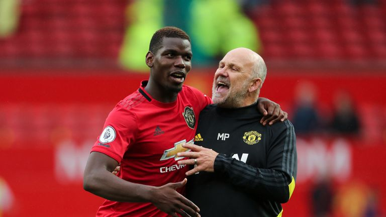 Paul Pogba celebrates the 4-0 win over Chelsea with Manchester United assistant manager Mike Phelan