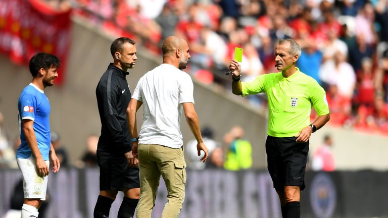 Pep Guardiola is booked for his touchline tirade on fourth official Stuart Atwell
