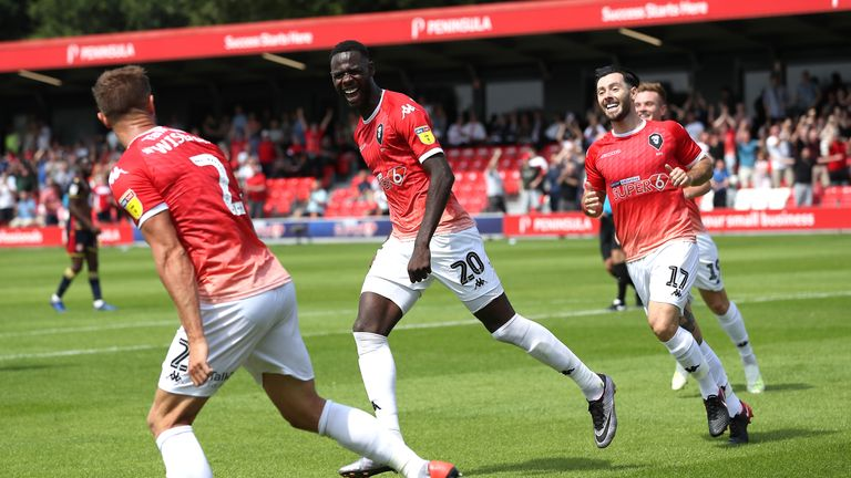 "Salford City's Mani Dieseruvwe (centre) celebrates scoring his side's first goal of the game with team mates during the Sky Bet League Two match at the Peninsula Stadium, Salford. PRESS ASSOCIATION Photo. Picture date: Saturday August 3, 2019. Photo credit should read: Martin Rickett/PA Wire. RESTRICTIONS: EDITORIAL USE ONLY No use with unauthorised audio, video, data, fixture lists, club/league logos or ""live"" services. Online in-match use limited to 120 images, no video emulation. No use in betting, games or single club/league/player publications."
