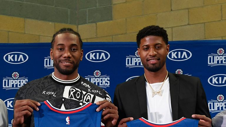 Kawhi Leonard and Paul George pose with their Clippers jerseys
