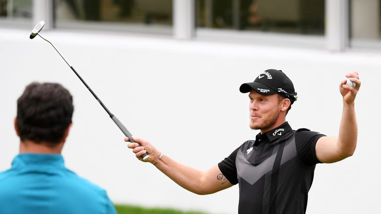 Danny Willett takes the acclaim of the crowd on the 18th green at Wentworth as Jon Rahm watches on