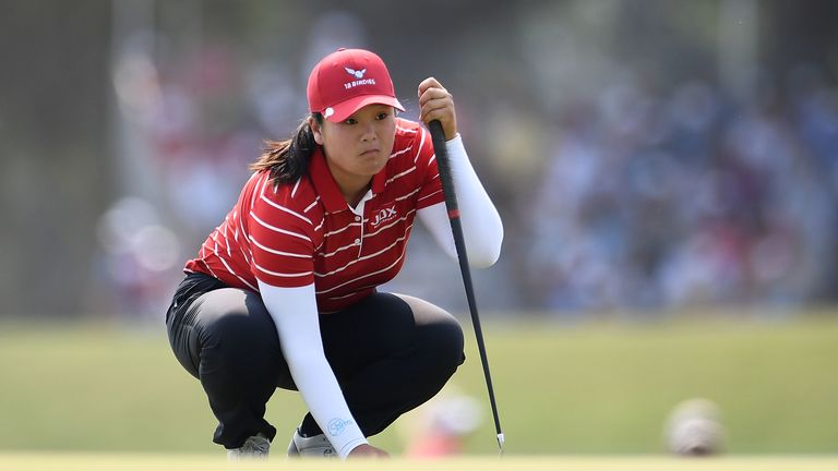 Angel Yin practiced alone on the range with borrowed clubs