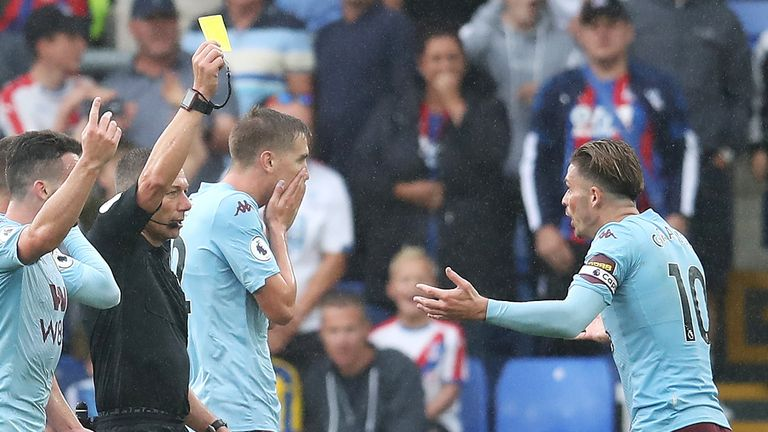 Match referee Kevin Friend gives a yellow card to Jack Grealish of Aston Villa during the Premier League match between Crystal Palace and Aston Villa at Selhurst Park on August 31, 2019 in London, United Kingdom.