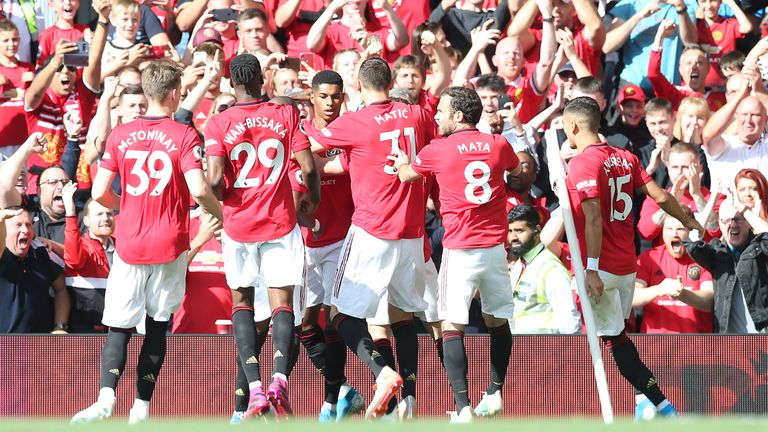 Marcus Rashford celebrates with team-mates after scoring his penalty
