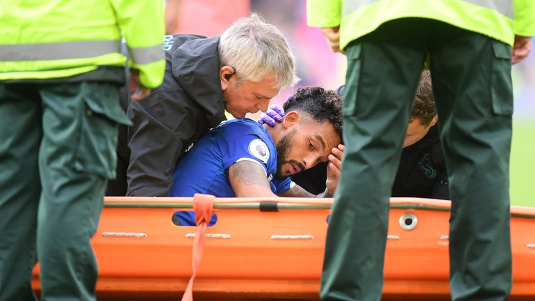Theo Walcott receives medical treatment after being hit on the head by a Raheem Sterling cross