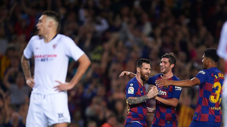 Lionel Messi celebrates with his Barcelona teammates after scoring against Sevilla