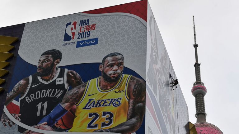 A worker removes a promotional banner from a building for the National Basketball Association (NBA) October 10 preseason game in China