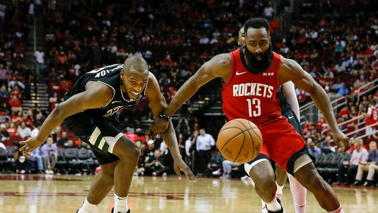 James Harden #13 of the Houston Rockets battles with Khris Middleton #22 of the Milwaukee Bucks for a loose ball in the second half at Toyota Center on October 24, 2019 in Houston, Texas