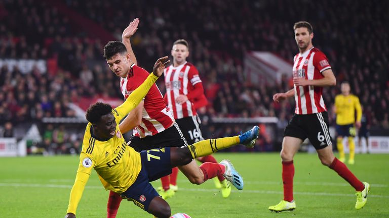 Bukayo Saka of Arsenal goes down after he battles for possession with John Egan of Sheffield United