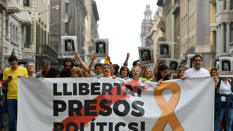 "Pro-independence supporters in Barcelona carry a banner reading ""Free political prisoners"" after their sentencing"