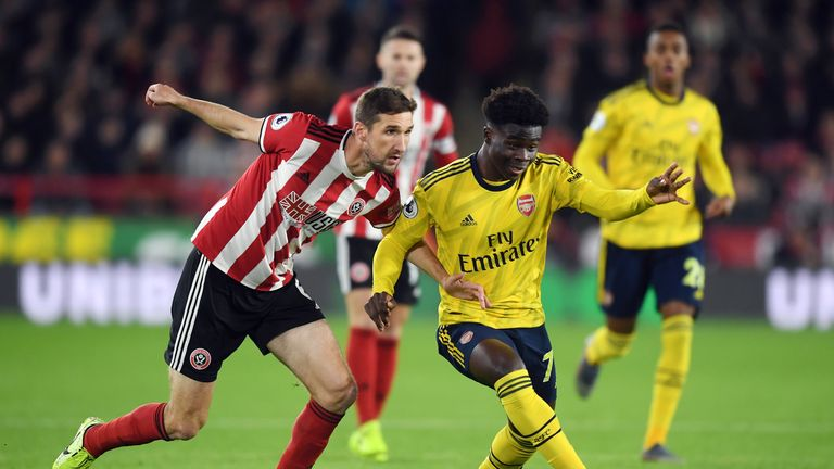 Chris Basham of Sheffield United battles for possession with Bukayo Saka of Arsenal