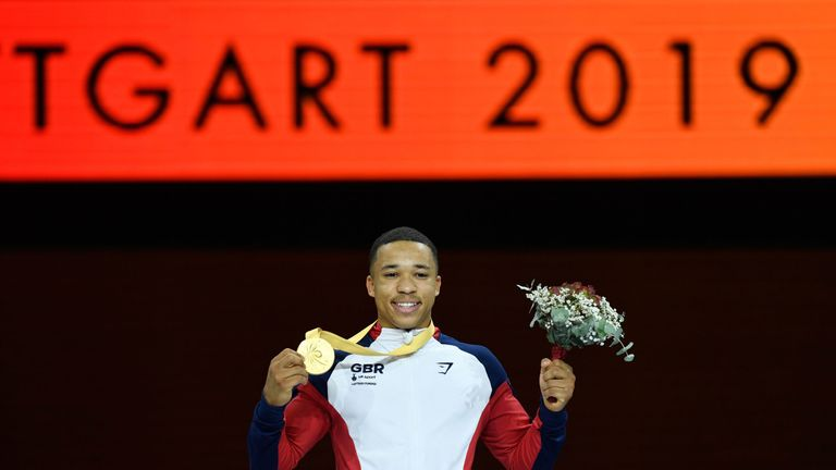 First placed Great Britain's Joe Fraser celebrates on the podium after the parallel bars event of the apparatus finals at the FIG Artistic Gymnastics World Championships at the Hanns-Martin-Schleyer-Halle in Stuttgart, southern Germany, on October 13, 2019.
