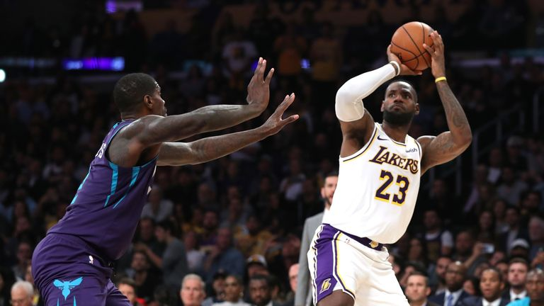 LeBron James of the Los Angeles Lakers shoots past the defense of Marvin Williams of the Charlotte Hornets