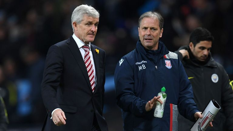 Stoke City's Welsh manager Mark Hughes (L) speaks with assistant manager Mark Bowen (R) as he leaves at half time in the English Premier League football match between Manchester City and Stoke City at the Etihad Stadium in Manchester, north west England, on March 8, 2017.