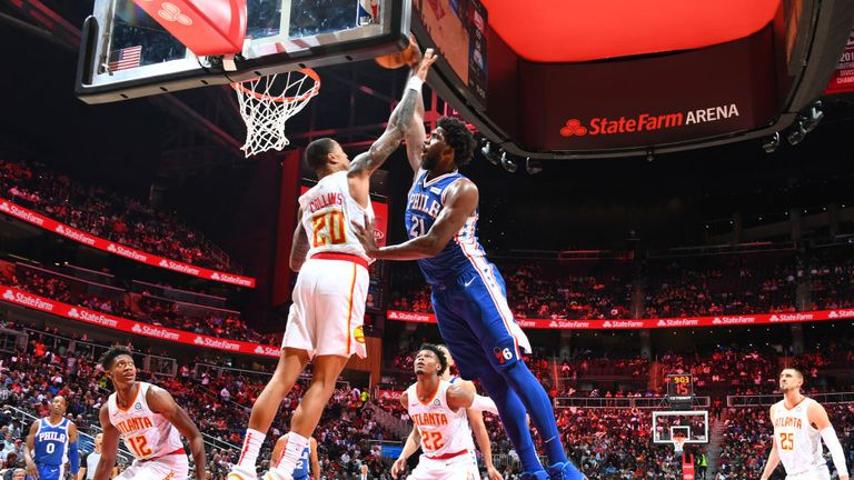 Joel Embiid of the Philadelphia 76ers dunks the ball against John Collins of the Atlanta Hawks