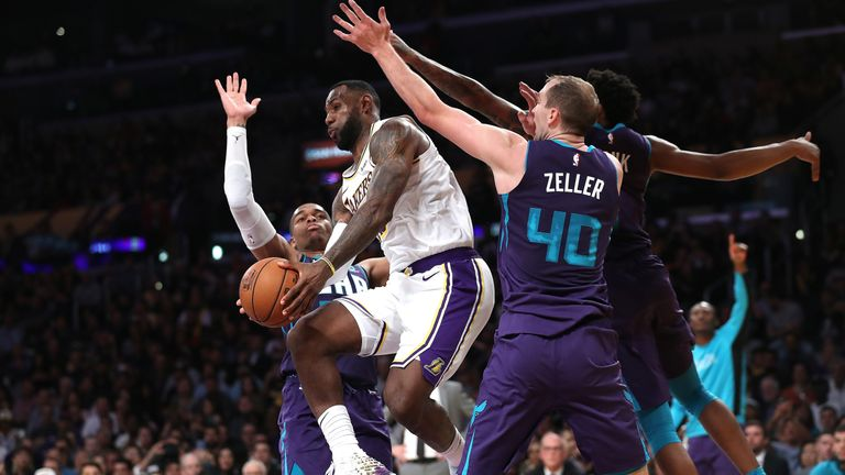 Cody Zeller , Malik Monk and PJ Washington of the Charlotte Hornets attempt to defend against LeBron James of the Los Angeles Lakers