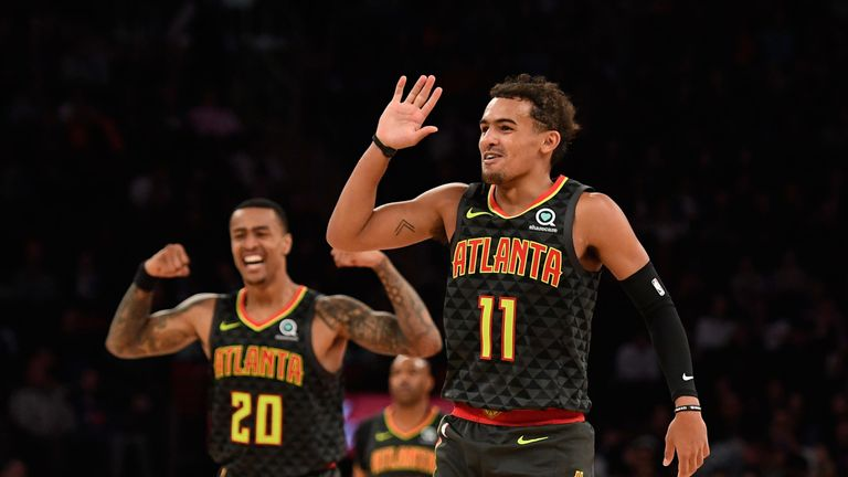 Trae Young celebrates after beating the buzzer from three-point land