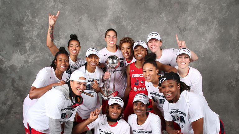The victorious Mystics pose with the WNBA trophy