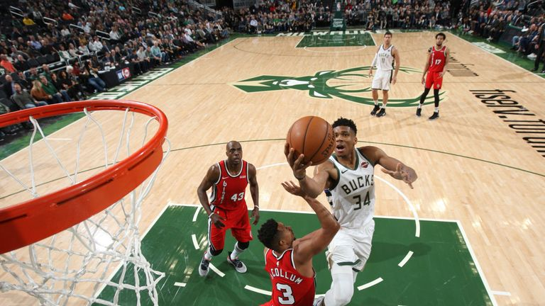 Giannis Antetokounmpo elevates over CJ McCollum to score at the rim