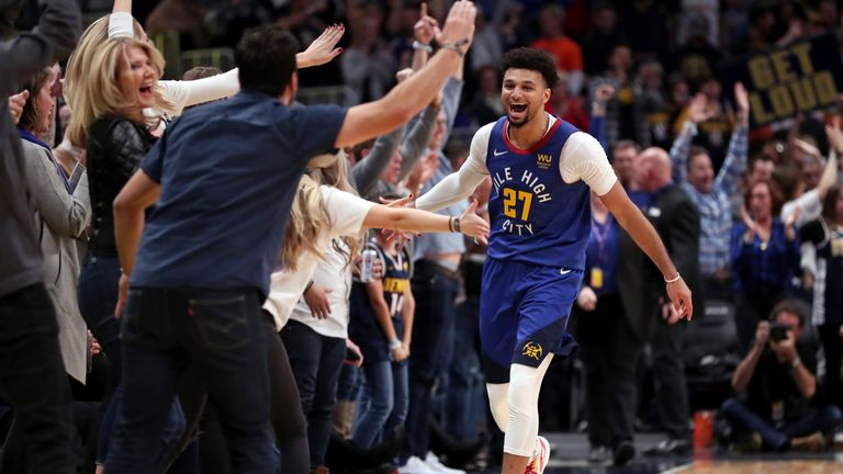 Jamal Murray celebrates a basket with the Nuggets fans at courtside