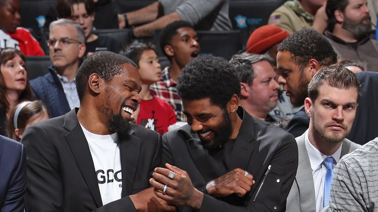 Kevin Durant and Kyrie Irving share a joke on the Brooklyn bench