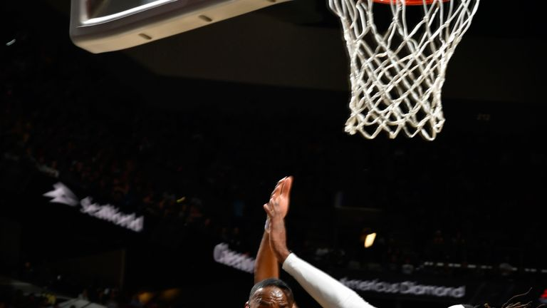 LeBron James goes airborne to pass against the the Spurs