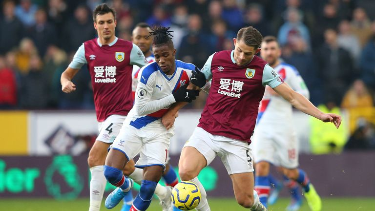 Crystal Palace's Wilfried Zaha challenges for the ball with Burnley's James Tarkowski