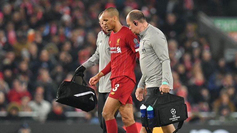 Liverpool's Brazilian midfielder Fabinho (C) leaves the pitch injured during the UEFA Champions league Group E football match between Liverpool and Napoli at Anfield