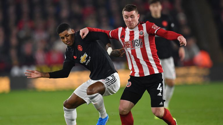 Manchester Unite forward Marcus Rashford battles for possession with Sheffield United midfielder John Fleck