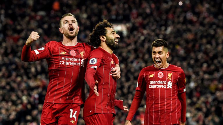 Mohamed Salah celebrates with Jordan Henderson and Roberto Firmino after doubling Liverpool's lead vs Man City at Anfield