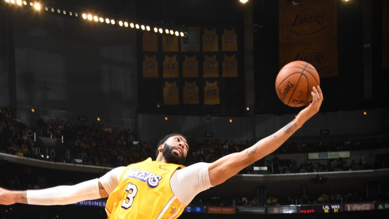 Lebron James watches on as Anthony Davis stretches his incredible frame to grab a rebound in the Lakers' win over the Wizards