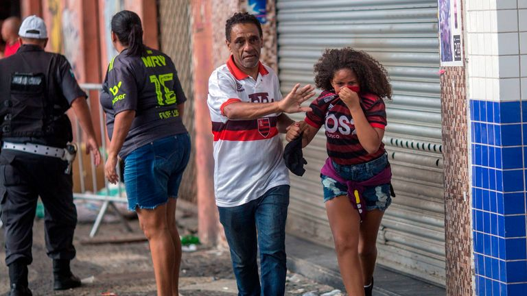 Supporters flee from tear gas shot by riot police