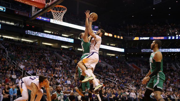 Tyler Johnson of the Phoenix Suns attempts a shot over Carsen Edwards of the Boston Celtics
