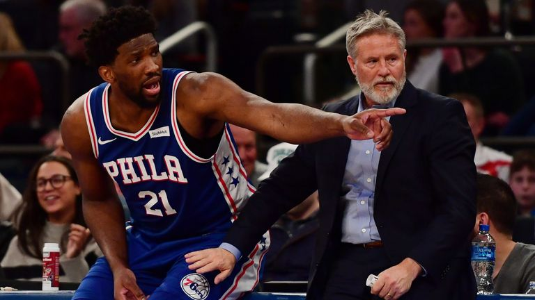 Joel Embiid questions a call from the scorer's table alongside Sixers coach Brett Brown