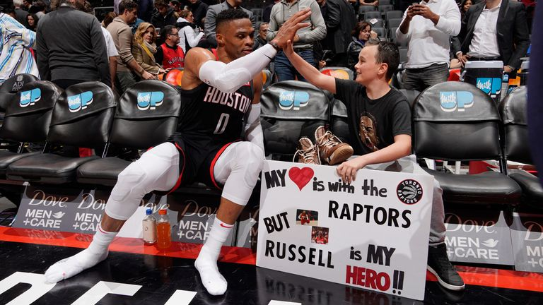 Russell Westbrook high-fives a fan in Toronto