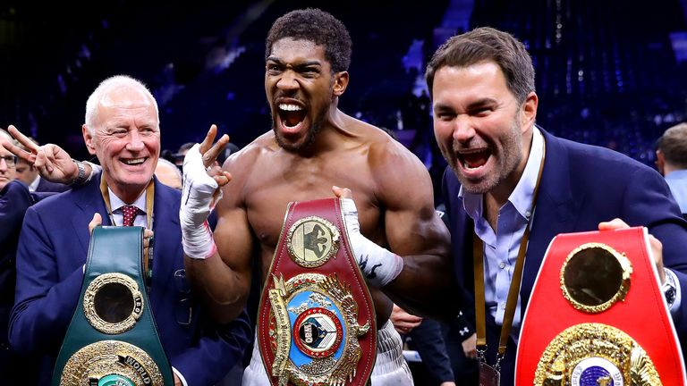 Joshua celebrates with Barry and Eddie Hearn