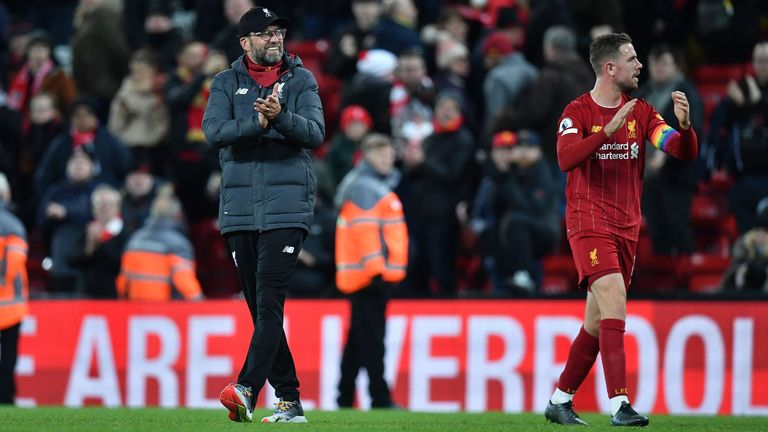 Liverpool's German manager Jurgen Klopp (L) and Liverpool's English midfielder Jordan Henderson applauds the fans following the English Premier League football match between Liverpool and Everton at Anfield in Liverpool, north west England on December 4, 2019. - Liverpool won the match 5-2.