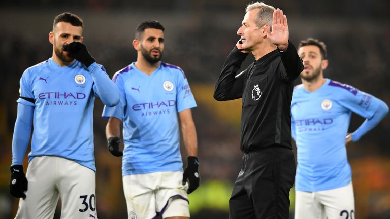 Martin Atkinson speaks with Stockley Park officials before VAR overturns his penalty decision