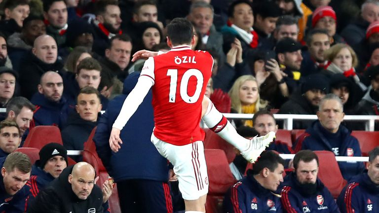 Mesut Ozil of Arsenal kicks a water bottle as he is subbed as Interim Manager of Arsenal, Freddie Ljungberg looks on during the Premier League match between Arsenal FC and Manchester City at Emirates Stadium on December 15, 2019 in London, United Kingdom.