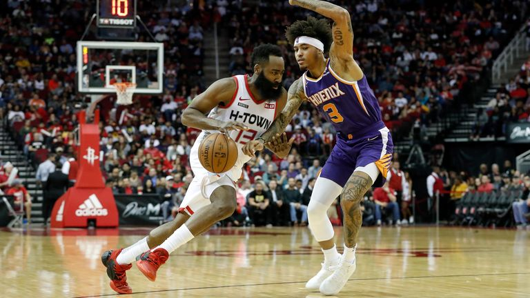 James Harden of the Houston Rockets drives to the basket defended by Kelly Oubre Jr. of the Phoenix Suns