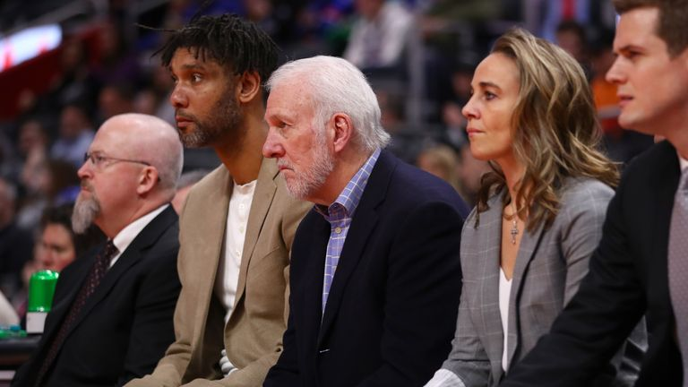 Head coach Gregg Popovich of the San Antonio Spurs looks on next to assistant coaches Becky Hammon and Tim Duncan