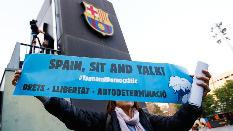 A woman holds up a banner with the words 'Tsunami Democratic' and 'Spain, Sit and Talk!' before the Liga match between Barcelona and Real Madrid