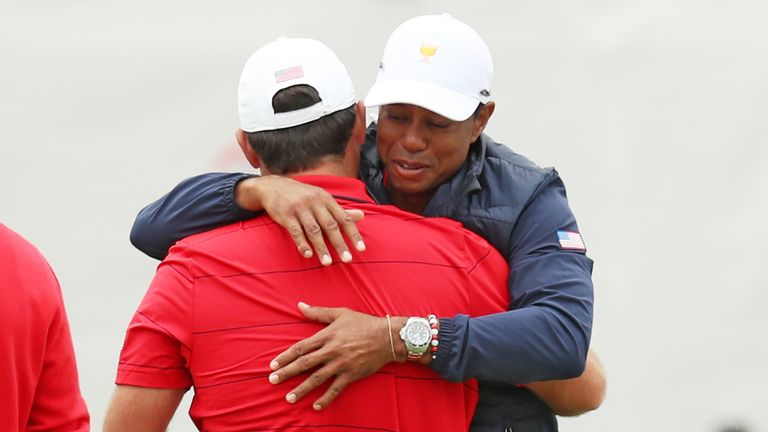 Tiger Woods embraces Reed after his singles victory