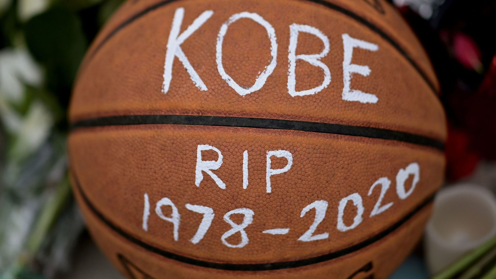 A basketball with the message 'KOBE RIP 1978-2020' is left amongst floral tributes outside Bryant Gymnasium at Lower Merion High School