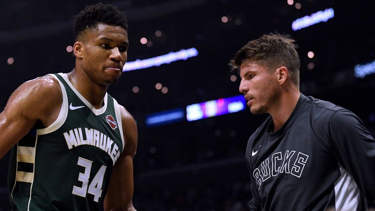 Giannis Antetokounmpo high-fives Bucks team-mate Kyle Korver