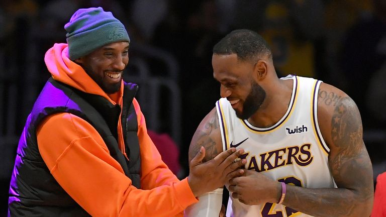 Kobe Bryant and LeBron James share a joke courtside during a Lakers game